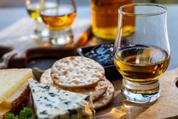 Whiskey and cheese pairing, tasting whisky glasses and plate with sliced cheeses close up