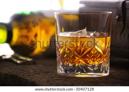 Whiskey and ice in a glass with the bottle in background