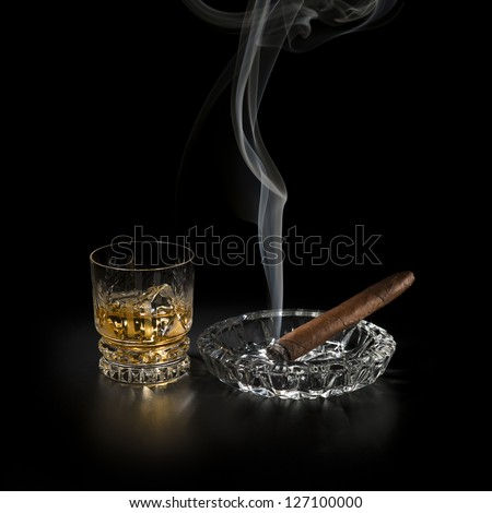 Whiskey and smoking cigar on black background close up