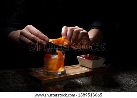 Whiskey based cocktail - closeup of bartender hands preparing Old Fashioned Whiskey Cocktail on bar counter.