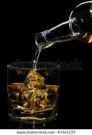 Whiskey being poured into a glass against black background #43365259