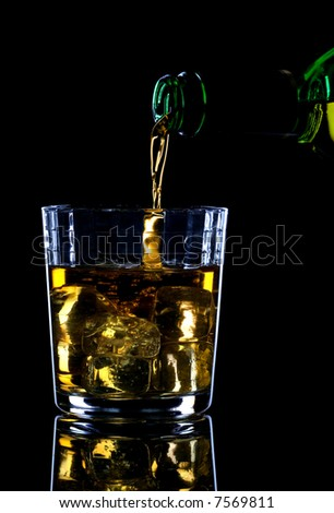 Whiskey being poured into a glass of ice against a black background. #7569811