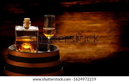 Whiskey bottle and whiskey glass stand on a whiskey barrel, whiskey drink in the distillery