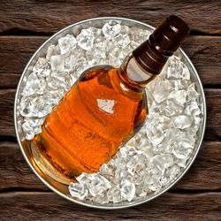 Whiskey bottle in ice bucket from top view on wooden background including clipping path