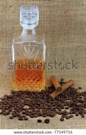 Whiskey, coffee and cigars. Picture of decorative crystal glass bottle contains whiskey, coffee beans and two cigars over burlap background.