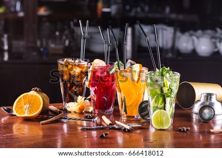 Whiskey-cola cocktail, mojito-cocktail, orange cocktail, strawberry cocktail in glass glasses with straws. Bar accessories: shaker, spoon, spices on a wooden stand