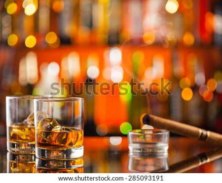 Whiskey drinks on bar counter with blur bottles on background