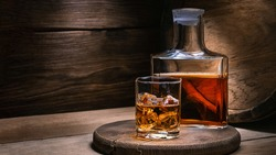 Whiskey drinks. You need to drink whiskey with ice then the whiskey tastes better of an oak barrel. Alcoholic drink with ice whiskey or cognac close-up on an oak coaster for glasses for spirits.