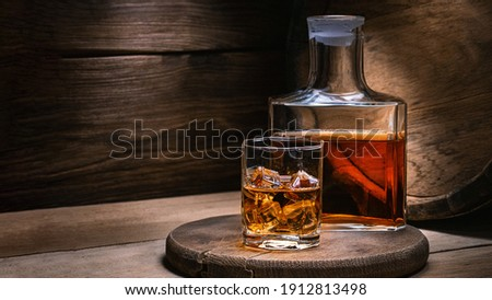 Whiskey drinks. You need to drink whiskey with ice then the whiskey tastes better of an oak barrel. Alcoholic drink with ice whiskey or cognac close-up on an oak coaster for glasses for spirits. Foto stock ©