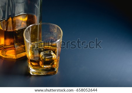 Whiskey glass and bottle on black and blue surface. #658052644