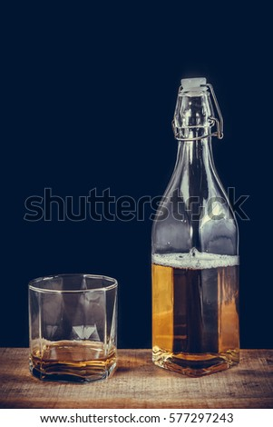 Whiskey glass and bottle on the old wooden table #577297243