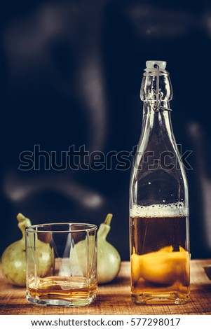 Whiskey glass and bottle on the old wooden table with calabash #577298017