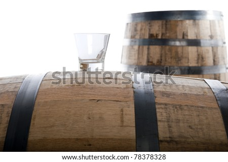 Whiskey glass on a whiskey barrel with a second barrel in the distance, isolated on white, selective focus on glass
