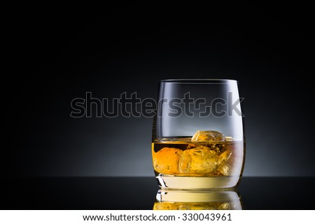 Whiskey glass on black glass surface