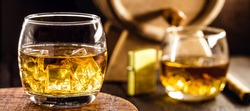 whiskey glass with ice, spot focus, bottle, lighter and barrel on blurred background. Distilled drink with malt