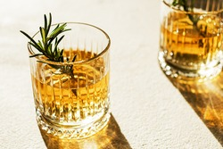Whiskey in a glass decorating with rosemary.the sun's rays pass through the glass. High quality photo