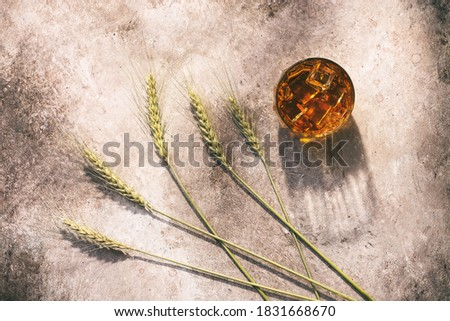 Whiskey in a glass with ice and ears of wheat or rye in the sunlight with long shadows on a beige rustic background. Top view, flat lay ストックフォト ©