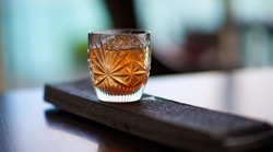 whiskey in the crystal glass on barrel wood plank
