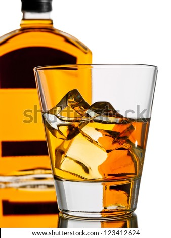 Whiskey on the rocks with a bottle on the background