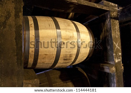 Whiskey or bourbon barrels aging in old distillery warehouse