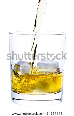 Whiskey pouring into a glass isolated on white