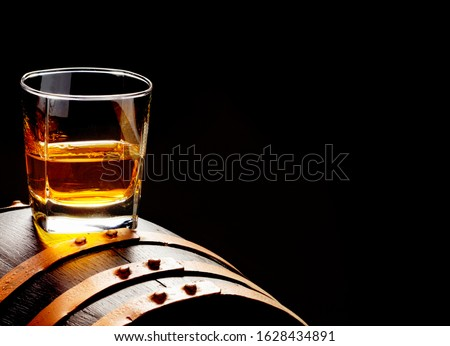 Whiskey sample, whiskey glass stands on a whiskey barrel