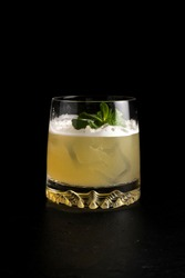 Whiskey sour cocktail. Cold alcoholic cocktail of quail egg protein, lemon juice, sugar syrup, bourbon, bitter, mint and ice in a transparent glass on a black background.
