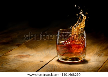 Whiskey splash in glass on a wooden table. #1101468290