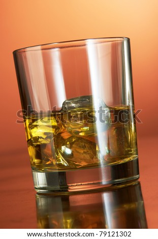 Whiskey with ice cubes on red background #79121302