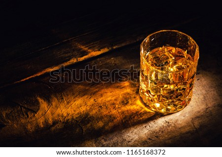 whiskey with ice cubes on wooden background