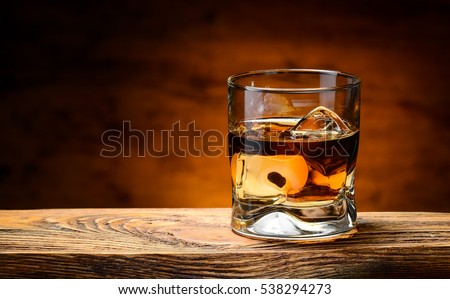 whiskey with ice on a wooden table #538294273