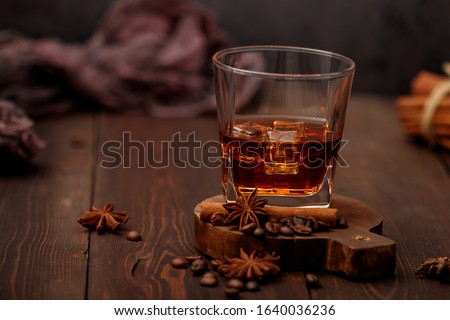 Whiskey with ice or brandy in a glass on a rustic background. Whiskey with ice in a glass. Whiskey or brandy. Selective focus.