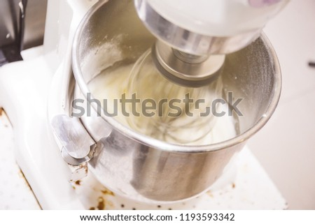 Whisking and stirring machine mixing raw eggs and flour together - with motion blur on utensil whisk #1193593342