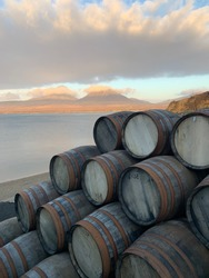 Whisky barrels with he paps of Jura as a background, outside the Bunnahabin Distillery on the island of Islay, the west coast of Scotland.