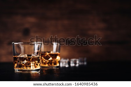 Whisky, bourbon or cognac with ice cubes on black stone table and wood background ストックフォト ©