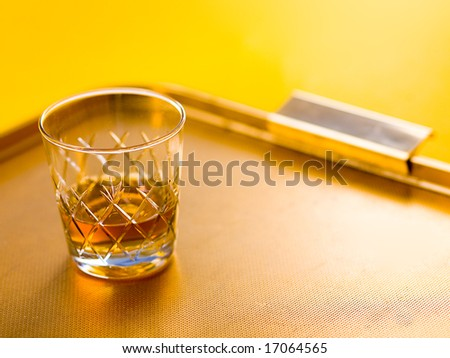 Whisky glass on yellow tray