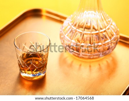 Whisky glass on yellow tray with de canter