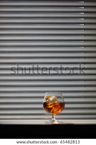 Whisky glass with ice on a window sill