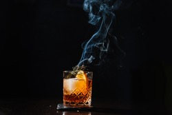 Whisky & Smoke. Smoking whiskey with ice and orange on a dark background. Cognac with smoking branch of lavender. Experimental alcoholic cocktail in a glass with smoking rosemary.