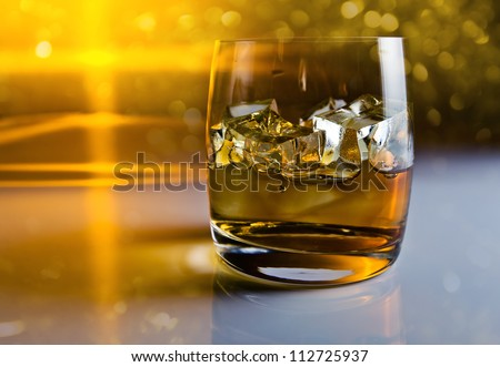 whisky with ice on a reflective background