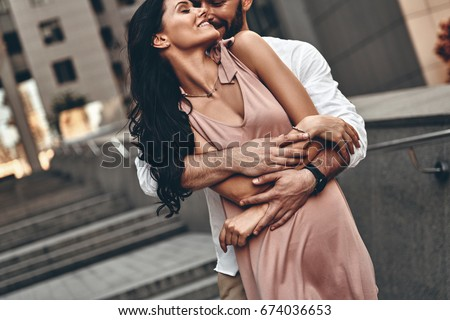Whispering about love. Handsome young man embracing his beautiful girlfriend while spending time together in the city