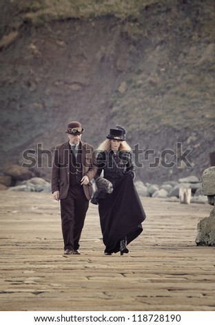 WHITBY, UK - NOV 4: A man and woman stroll along the promenade in Victorian clothing celebrating the famous Goff Weekend at Whitby, England on November 4, 2012.