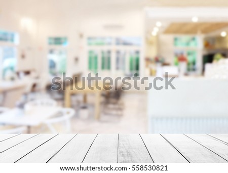 Shutterstock White above wood floor focus to table top in the foreground. Abstract blurred of restaurant shop pastel background. Counter cafes and coffee service. Food and Beverage Modern.