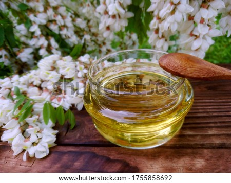 Photo of  White acacia honey jar, flowers & green leaf on wooden background. Spring acacia white flowers. Robinia pseudoacacia (white acacia) tree honey close up. Raw honey spring flowers, wood spoon, top view