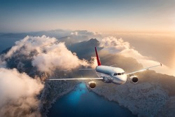 White airplane is flying over mountains and low clouds at sunset in summer. Landscape with beautiful passenger airplane, sky in clouds, sea, sunlight. Travel. Commercial plane. Aerial view of aircraft