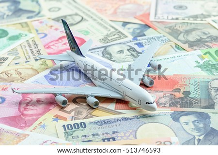 White airplane lands on a pile of banknotes from the most dominant countries around the world i.e. US dollar, Chinese CNY yuan, Japanese yen, Indian rupee, Australian dollar, Euro. Aviation concept.