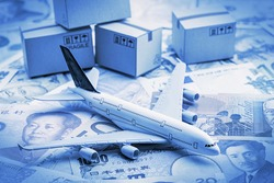 White airplane lands on notes from the most famous countries around the world with carton of goods behind. An idea of things about aviation i.e. overseas freight forwarding, express courier services.