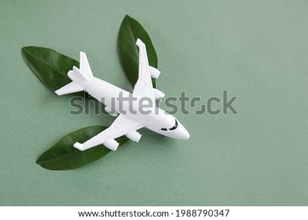 White airplane model emitting fresh green leaves on green background. Sustainable travel, clean and green energy, biofuel for aviation industry concept. Copy space Foto stock ©