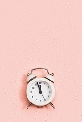 White alarm clock shows about twelve oсlock on pink paper background covered with sequins with copy space. New year Christmas concept. Flat lay. Top view.