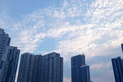 White Altocumulus Clouds Scattered on Light Blue Sky over the Group of Skyscrapers